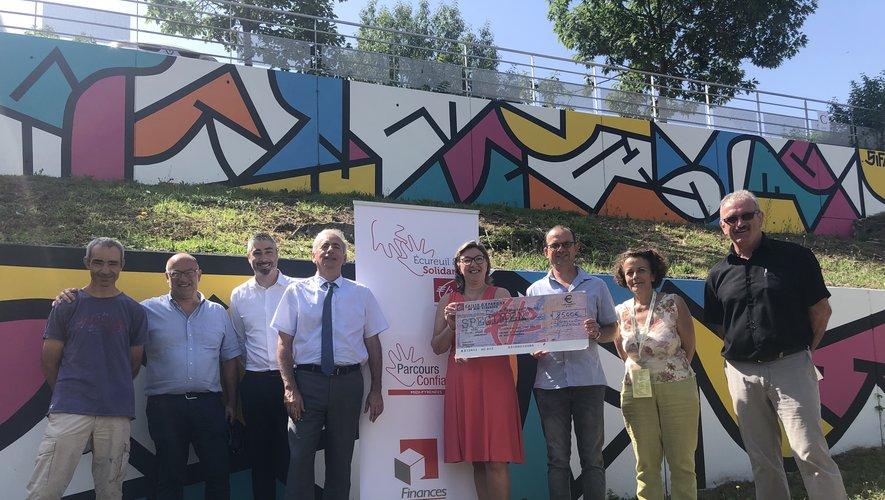 La présidente de la Caisse d'épargne remet un chèque au président d'ART, sous la fresque de Sifap à Decazeville communauté./Photo DDM