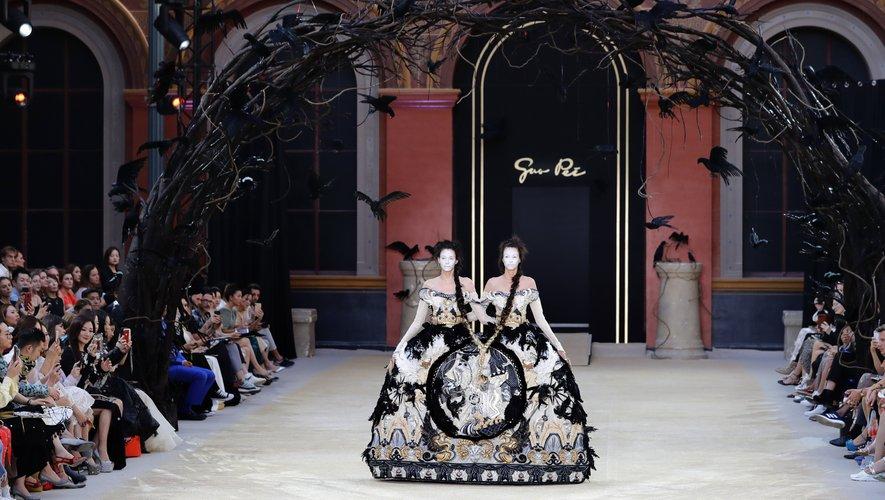 Impressionnante robe confectionnée pour accueillir des sœurs siamoises, non seulement liées par leur tenue mais également par leurs tresses longueur XXL, chez Guo Pei. Paris, le 3 juillet 2019.