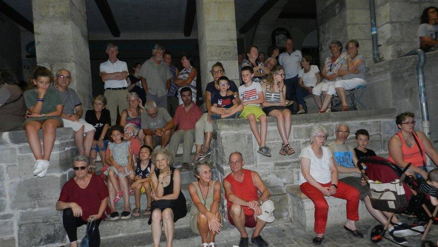 Assis sur les marches entre les arcades et la place, le public apprécie le spectacle.