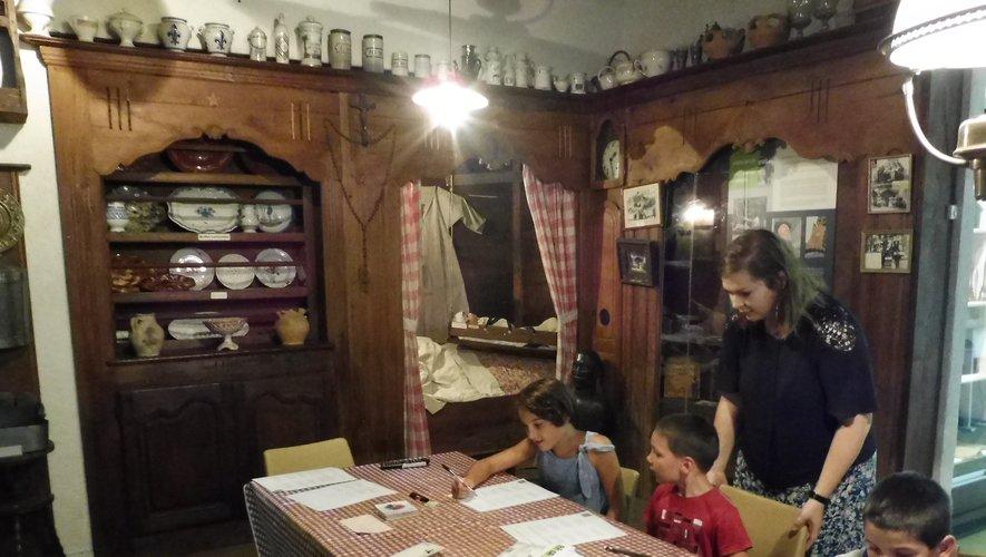 Les enfants à  l'Oustal, un intérieur traditionnel rouergat du XIXe siècle avec le cantou et son ensemble mobilier.