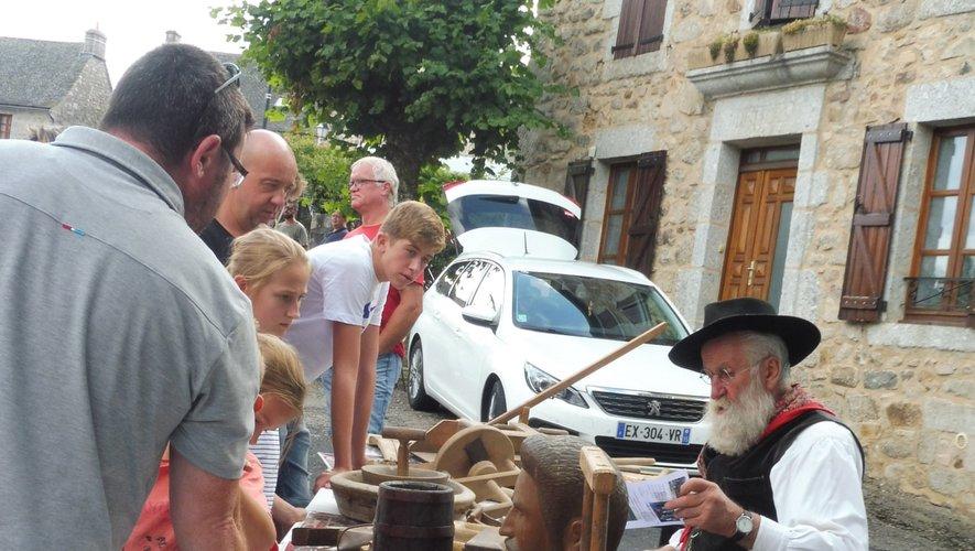Capou explique aux jeunes l'utilité de divers objets anciens en bois.
