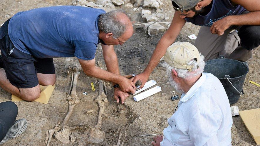 Philippe Gruat (en bleu) au pied du squelette découvert lors de cette campagne de fouilles.