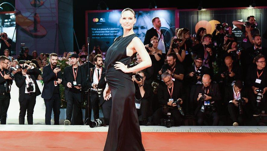 La top Bar Refaeli a opté pour le chic intemporel d'une longue robe noire, avec des jeux de superposition, pour ce second tapis rouge. Venise, le 29 août 2019.