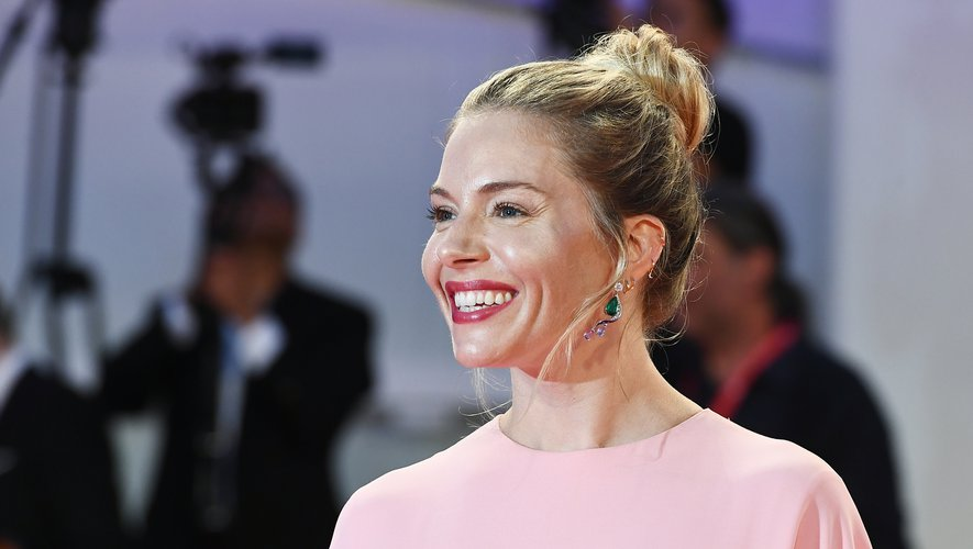 """L'actrice Sienna Miller arborait un chignon haut pour la projection du film """"The Laundromat"""", le  1er septembre. La coiffure est associée à un teint frais comme la rosée et à une bouche rouge."""