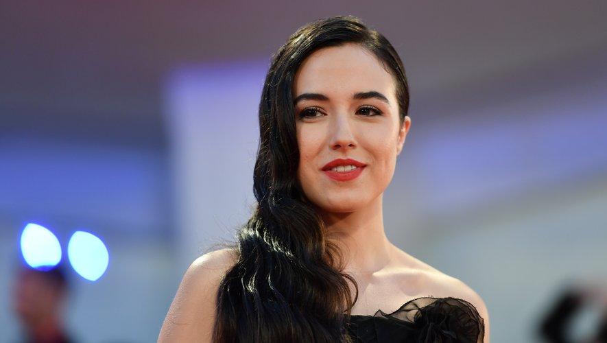 """L'actrice italienne Denise Sardisco a opté pour une bouche rouge et des cils très travaillés pour la projection de """"Martin Eden"""". Un chevelure effet mouillé, coiffée sur le côté, renforce l'effet glamour de l'ensemble."""