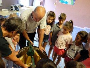 Les enfants assistent à la récolte du miel.