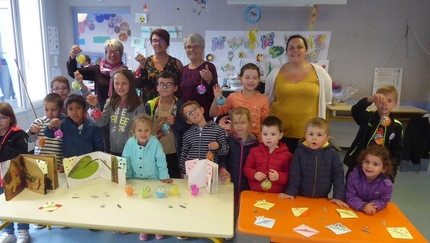 Les enfants et leurs animatrices présentant les objets réalisés aux responsables du Téléthon.