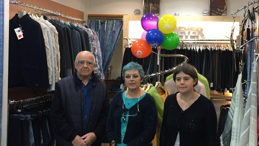Nadine Gratacap entourée par Jacques Camboulives, l'ancien propriétaire, et Aurélie, la vendeuse-retoucheuse, se prépare à souffler les 80 bougies de son enseigne.