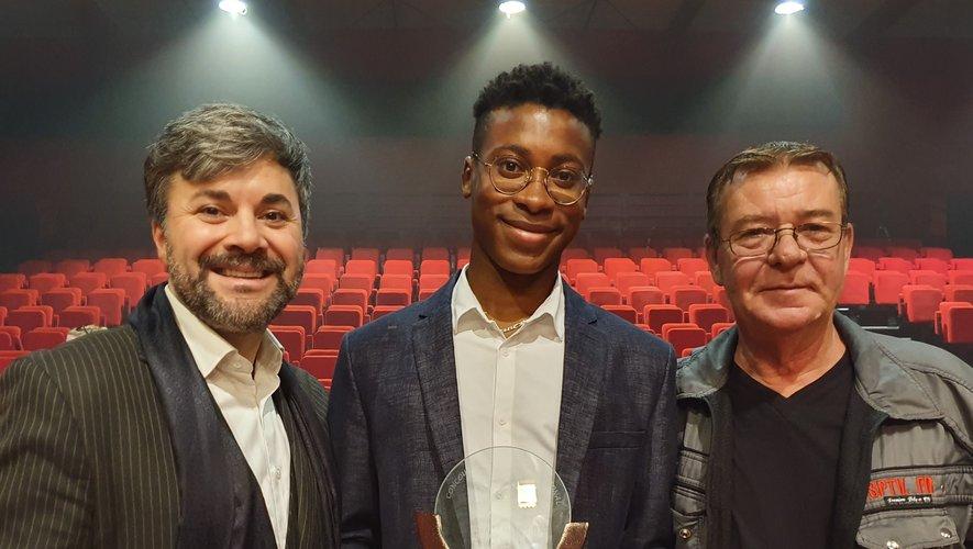 Auguste tenant son trophée et entouré d'Alexandre Chassagnac, son professeur de chant, et de Didier Champ, de la Maison de disques NSP Record.