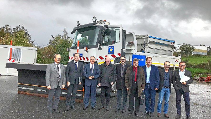 Aux côtés du président Galliard et des élus, l'équipe de la direction des routes devant une saleuse munie d'une étrave destinée à la viabilité hivernale.