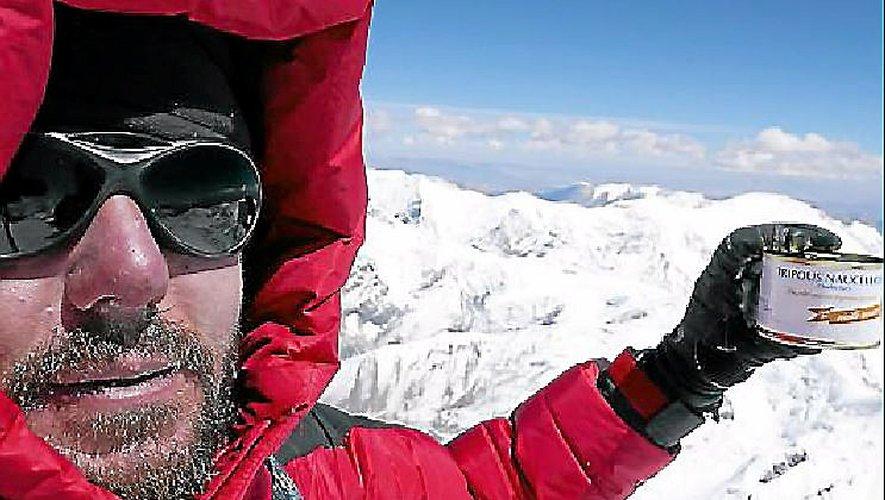 Bertrand Vayssettes lors de son ascension de l'Himlung, une boîte de tripous à la main.