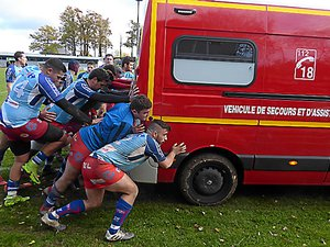 Les rugbymen poussant le véhicule des pompiers, comme en mêlée