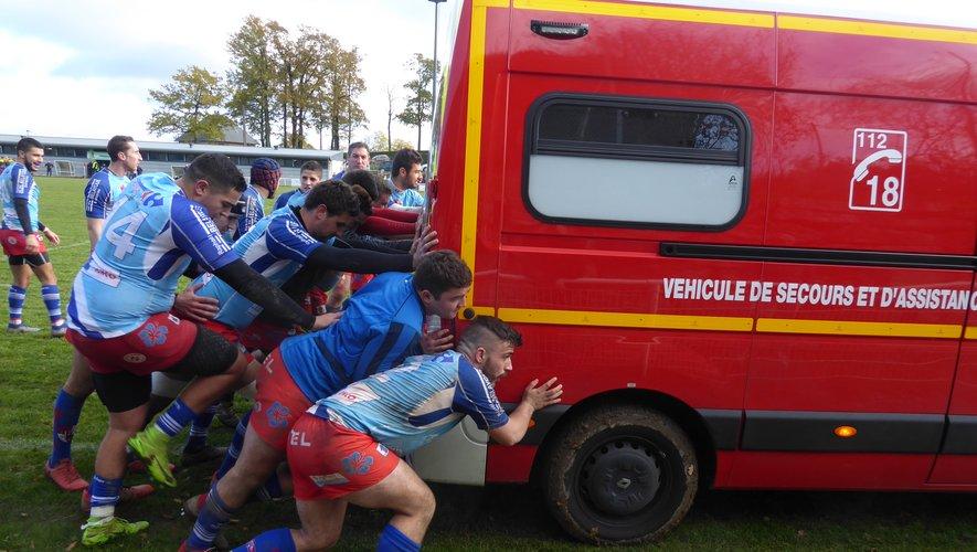 Les rugbymen poussent le véhicule des pompiers pour rejoindre le blessé.