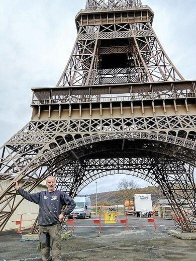 Alain Lacombe au pied de « sa » tour Eiffel de 28 mètres et 10 tonnes, une magnifique et saisissante reproduction à l'identique de l'original, à l'échelle 1/15e.