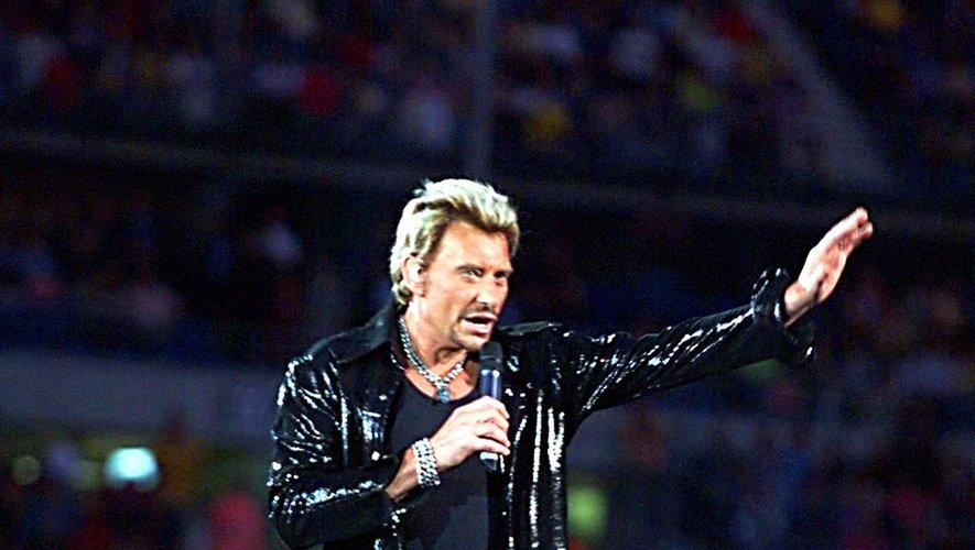 Johnny Hallyday fait un geste en direction du public venu l'écouter, le 05 septembre 1998 au Stade de France de Saint-Denis, lors du premier concert de la star devant 70.000 spectateurs