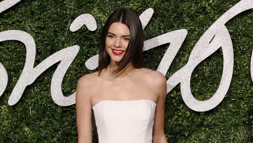 Kendall Jenner fait une arrivée remarquée aux Fashion Awards 2014 dans une combinaison blanche ornée de bandes noires latérales, signée Emilio Pucci.