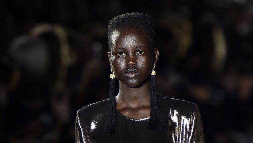 Adut Akech fait ses premiers pas de mannequin sur le podium de la maison Saint Laurent, en exclusivité, assurant le show dans une sublime robe en lamé. Le début d'une carrière. Paris, le 27 septembre 2016.