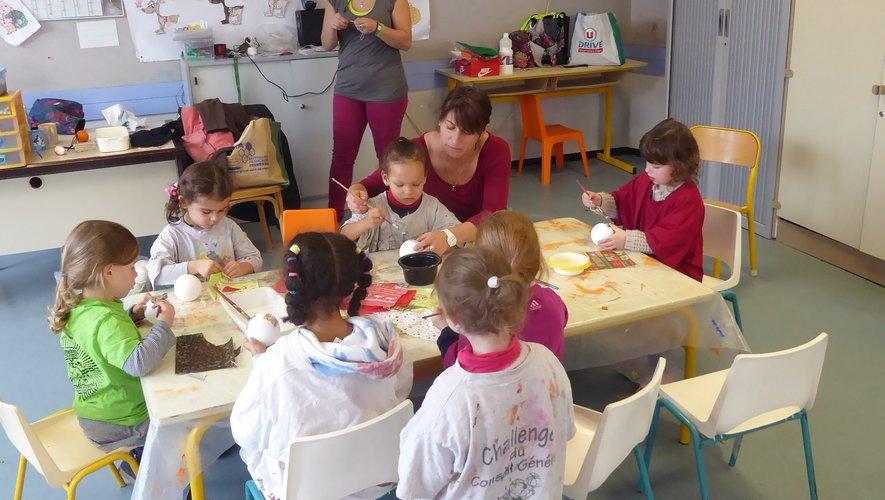 Un groupe d'enfants confectionnant des boules avec Marie et Marion.