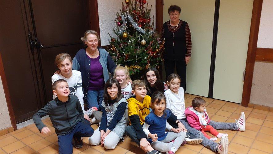 Des enfants heureux de faire plaisir en cette veille de Noël.