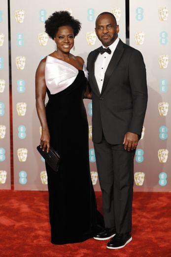 Elégants et glamour. Voici comment on pourrait qualifier Viola Davis et Julius Tennon qui ont choisi des looks noirs et blancs. On adore d'ailleurs le noeud blanc qui vient rehausser la robe de Viola pour les BAFTA. Londres, le 10 février 2019.