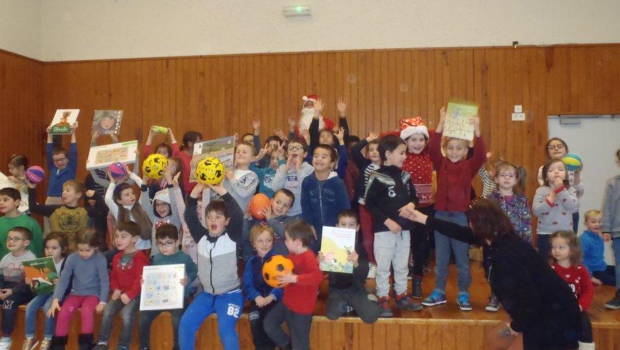 Les enfants posent avec le père Noël et présentent les cadeaux.