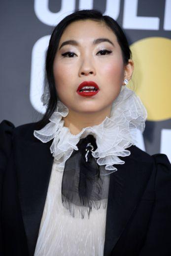 """Les lèvres rouges d'Awkwafina, ses paupières métallisées et son trait d'eyeliner ont constitué un sans faute, surtout que l'actrice a remporté le prix de la meilleure actrice pour le film """"L'Adieu""""."""