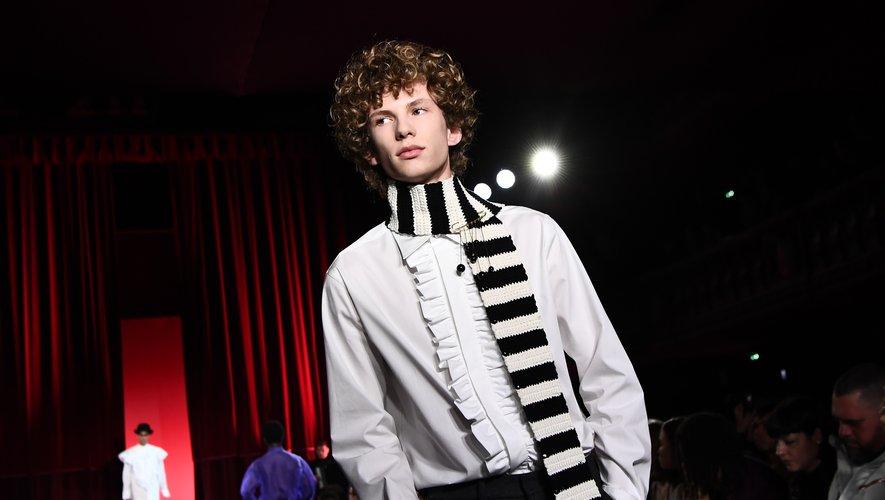 L'homme AMI by Alexandre Mattiussi déambule avec une chemise à jabot blanche, tout en élégance, agrémentée d'une écharpe rayée portée nonchalamment pour la touche romantique. Paris, le 14 janvier 2020.