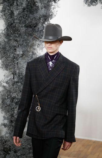 """Nouveau sur le calendrier officiel du prêt-à-porter homme, la maison Givenchy a décidé d'interpréter les traditions """"avec spontanéité"""". Des blazers et manteaux cintrés portés sur des pull en latex aux couleurs de pierres précieuses sont fermés"""