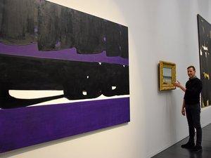 Christophe Hazemann présentant « le bord de merà Palavas » de Gustave Courbet et une œuvre de Soulages.