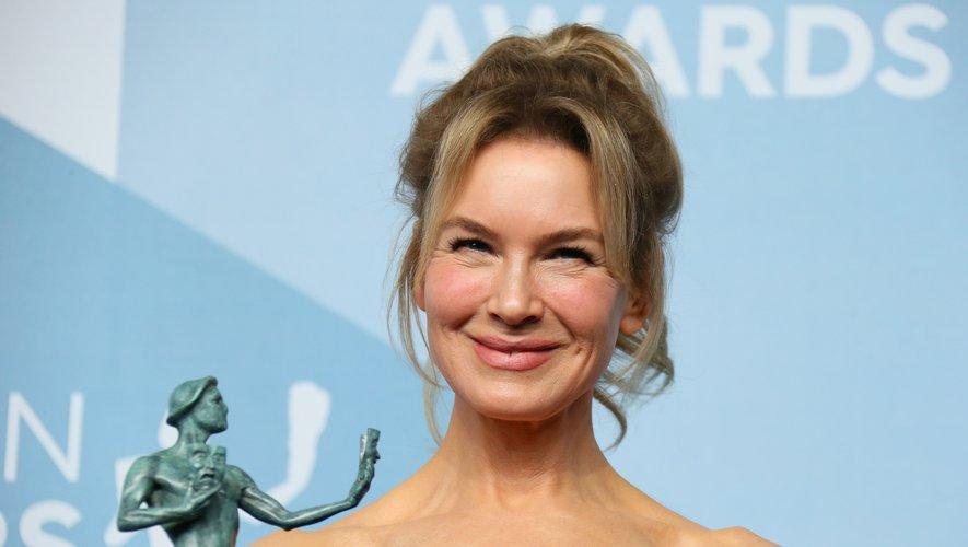 Renee Zellweger choisit aussi une coiffure 90's constituée d'une queue de cheval haute et de quelques mèches folles légèrement ondulées.