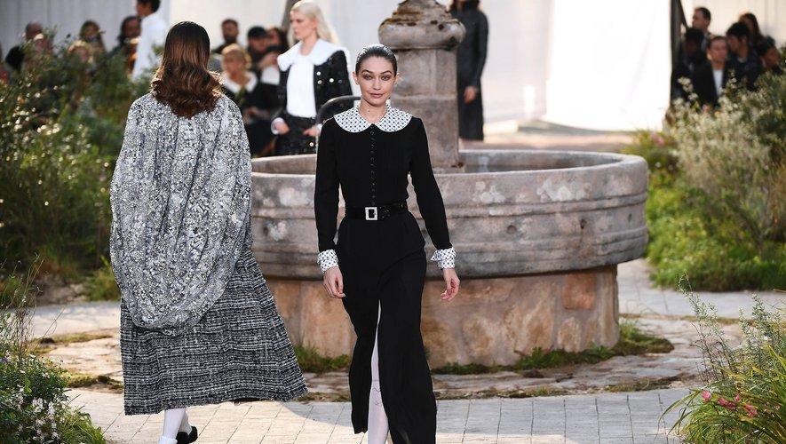 Très sage, la top Gigi Hadid est habillée en robe noire longue garnie d'un col Claudine et manches avec cols et manches blanches