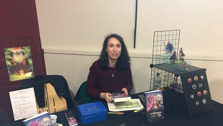 Barbara avec son livre et ses produits dérivés.