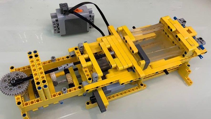 """Equipé d'une roue et relié par une batterie, cet outil jaune et gris construit à partir de 326 pièces de LEGO est également doté d'une boîte en silicone, permettant un procédé dit de """"cell stretching"""" qui stimule des cellules en culture."""