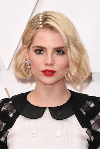 Non contente d'afficher des cils de poupée et une bouche rouge très glamour, Lucy Boynton agrémente sa raie sur le côté d'imposantes perles.