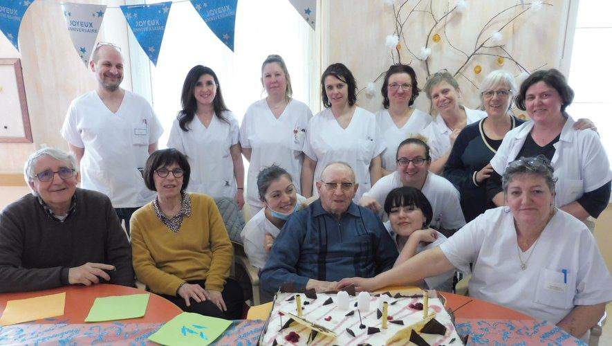 Maurice Barrau, entouré de son fils et de sa belle-fille, ainsi que du personnel de la  maison de retraite, devant le gâteau d'anniversaire.