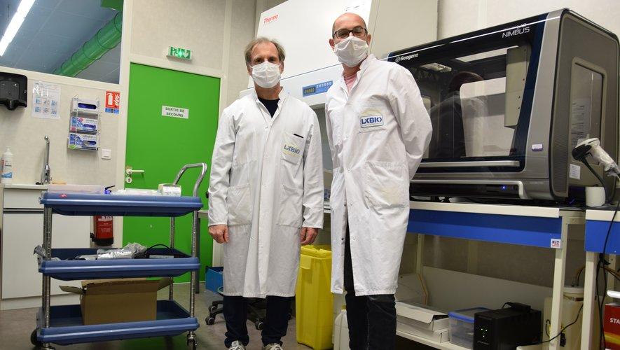 Jean-Pierre Bouilloux, PDG de LxBIO, et Pascal Caudène, biologiste, devant l'automate permettant de réaliser les tests liés au Covid-19.