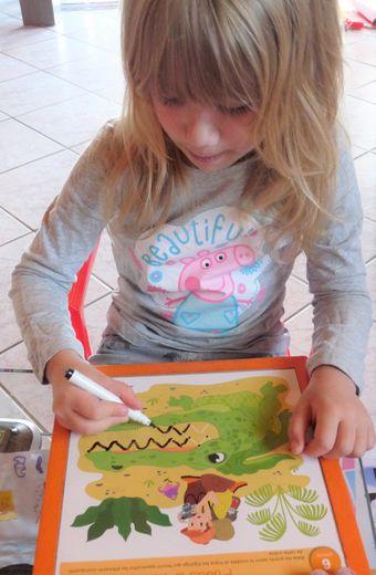 Chloé dessine et colorie.