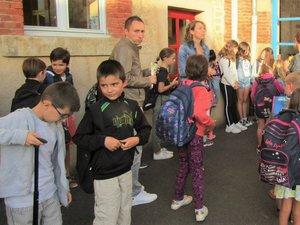 Les élèves ont quitté l'école les cartables remplis de cahiers et de livres.