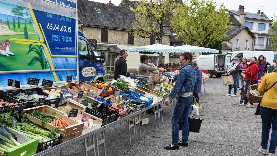 Devant l'étal du marchand de fruits et légumes et, ci-dessous, devant le fromager et le boucher.