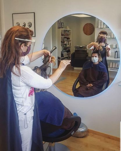 Sabine en train de coiffer une cliente tout en respectant les règles de sécurité.
