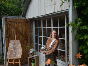 Morgane, devant sa boutique au pied de la cascade, présente quelques-unes de ses créations.
