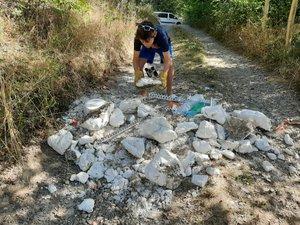Ce jeune garçon enlève les gravats déversés sur le chemin.