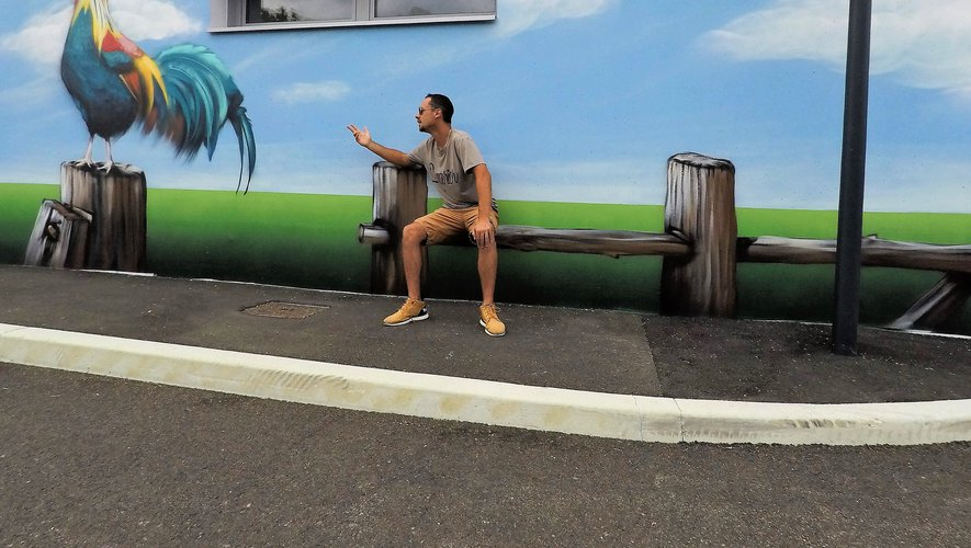 S'asseyant sur la barrière virtuelle, l'artiste joue avec le décor de son œuvre.