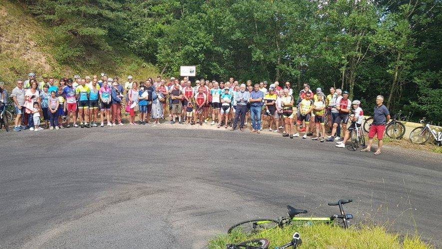 La famille et les cyclistes devant le panneau en mémoire de Christian Woittequand