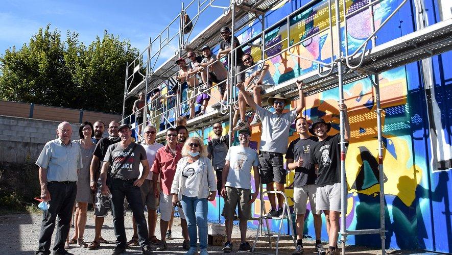 Artiste et compagnons devant la fresque street Art