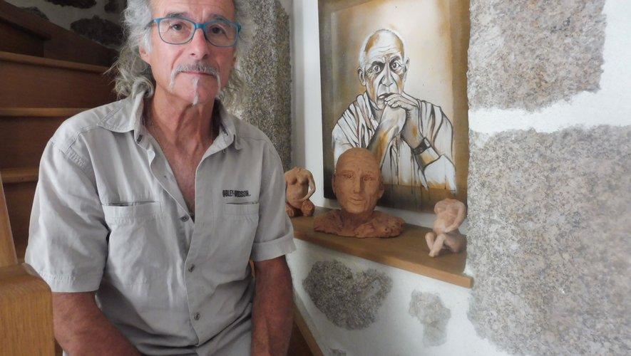 l'artiste avec un de ses tableaux et quelques sculptures.