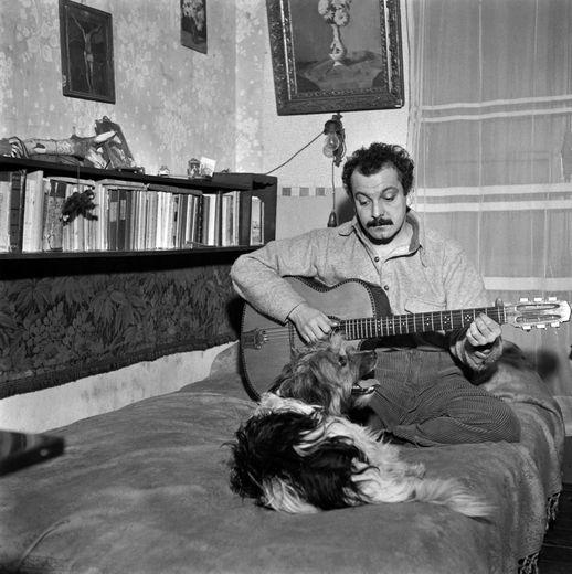 Le chanteur français Georges Brassens répète avec son chien dans une chambr