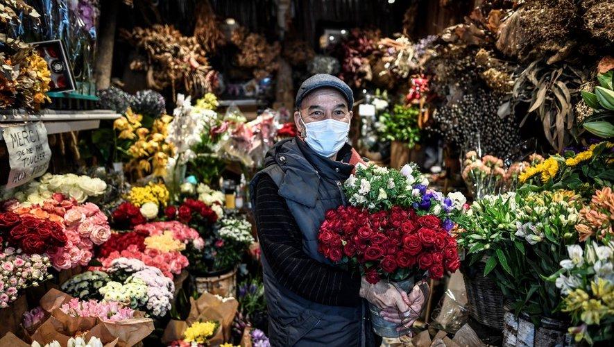 Un fleuriste portant un masque protecteur pose dans sa boutique à Paris le 27 novembre 2020, lors de la seconde fermeture de la France visant à freiner la propagation du Covid-19 (le nouveau coronavirus).
