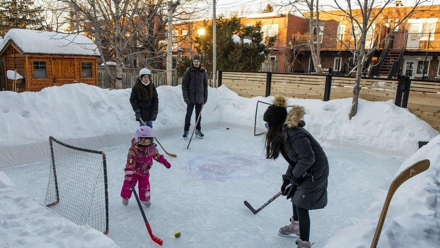 Comme ce père de famille, ils sont de plus en plus nombreux au Québec à construire une patinoire extérieure dans leur cour ou leur jardin, en raison du coronavirus, pour patiner ou jouer au hockey, le sport national au Canada.