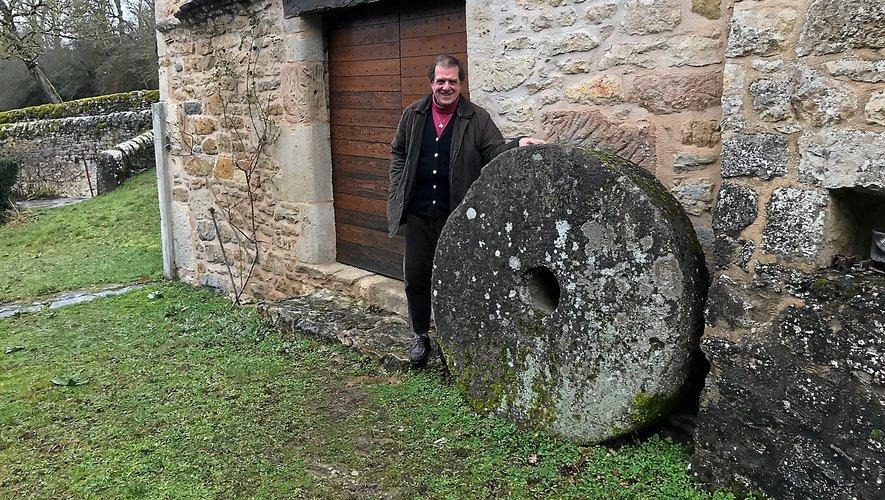 Devant son moulin du XVIe siècle et sa meule d'époque. La bâtisse sera le point de départ, en 1982, de sa passion pour les moulins. C.C.